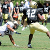"Josh Ford, 42, uses a spin move to escape Jermane Clarke, 30,during the University of Colorado Football team scrimmage on Saturday August 13, 2011.<br /> For more photos and video interviews from the scrimmage go to  <a href=""http://www.buffzone.com"">http://www.buffzone.com</a> and dailycamera.com<br /> Photo by Paul Aiken  August 13,  2011."
