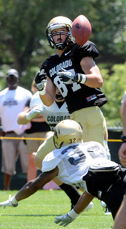 """Tyler McCulloch, 87, keeps his eye on the ball as he is defended by Paul Vigo, 32, during the University of Colorado Football team scrimmage on Saturday August 13, 2011.<br /> For more photos and video interviews from the scrimmage go to  <a href=""""http://www.buffzone.com"""">http://www.buffzone.com</a> and dailycamera.com<br /> Photo by Paul Aiken  August 13,  2011."""