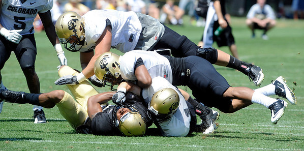 "DaVaughn Thornton, 85, gets tackled hard by Justin Gorman, 14, and Jonathan Hawkins, 18, during the University of Colorado Football team scrimmage on Saturday August 13, 2011.<br /> For more photos and video interviews from the scrimmage go to  <a href=""http://www.buffzone.com"">http://www.buffzone.com</a> and dailycamera.com<br /> Photo by Paul Aiken  August 13,  2011."