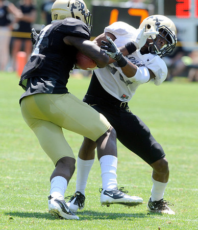 "Toney Clemons, 17, stiff arms, Ayodeji Olatoye, 25, during the University of Colorado Football team scrimmage on Saturday August 13, 2011.<br /> For more photos and video interviews from the scrimmage go to  <a href=""http://www.buffzone.com"">http://www.buffzone.com</a> and dailycamera.com<br /> Photo by Paul Aiken  August 13,  2011."