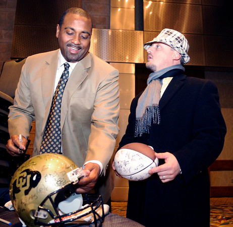 CUFootball010Recruiting.JPG University of Colorado head football coach Jon Embree signs a helmet for CU Alumnus Richmond Meyer, 35, during the University of Colorado Football Preview Luncheon on Thursday, Feb. 3, at the Hyatt Regency Denver Convention Center in Denver.<br /> Photo by Jeremy Papasso