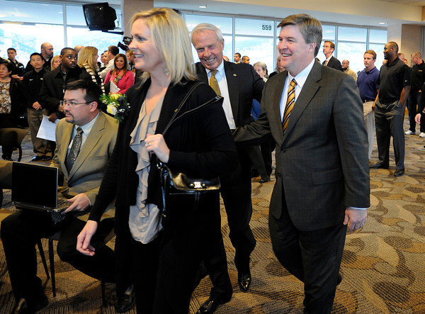"""The new University of Colorado head coach Mike MacIntyre, right, walks with CU President Bruce Benson, center, and his wife Trisha MacIntyre, left,  during a press conference in the club level of Folsom Field on Monday, Dec. 10, on the CU campus in Boulder. For more photos and video of the press conference go to  <a href=""""http://www.dailycamera.com"""">http://www.dailycamera.com</a><br /> Jeremy Papasso/ Camera"""