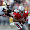 Colorado's Josh Hartigan, left, tries to sack Ohio State's Braxton Miller during the fourth quarter of an NCAA college football game Saturday, Sept. 24, 2011, in Columbus, Ohio. Ohio State defeated Colorado 37-17. (AP Photo/Jay LaPrete)