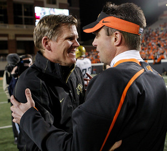 Colorado head coach Dan Hawkins, left, greets Oklahoma State head coach Mike Gundy, right, following of an NCAA college football game in Stillwater, Okla., Thursday, Nov. 19, 2009. Oklahoma State won the game 31-28. (AP Photo/Sue Ogrocki)