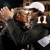 Colorado head coach Dan Hawkins, left, greets injured Oklahoma State quarterback Zac Robinson, right, following of an NCAA college football game in Stillwater, Okla., Thursday, Nov. 19, 2009. Oklahoma State won the game 31-28. (AP Photo/Sue Ogrocki)