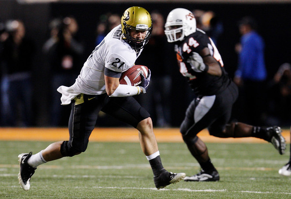 Colorado wide receiver Scotty McKnight carries the ball against Oklahoma State in the fourth quarter of an NCAA college football game in Stillwater, Okla., Thursday, Nov. 19, 2009. Oklahoma defender Donald Booker is at right. Oklahoma State won the game 31-28. (AP Photo/Sue Ogrocki)