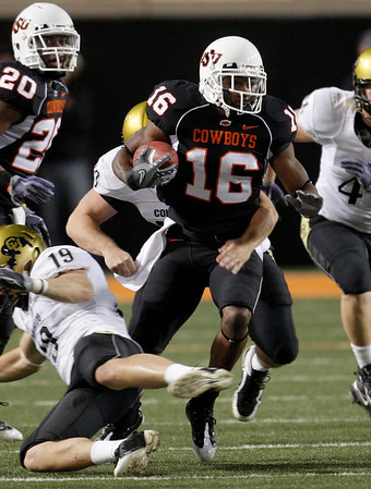 Oklahoma State's Perrish Cox, center, carries against Colorado in the second quarter of an NCAA college football game in Stillwater, Okla., Thursday, Nov. 19, 2009. Colorado's Travis Sandersfeld (19) falls to the field. (AP Photo/Sue Ogrocki)