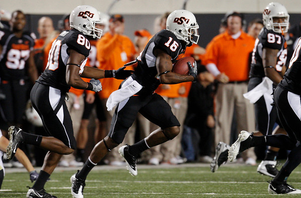 Oklahoma State's Perrish Cox, center, runs past his bench on his way to a touchdown against Colorado on a 67-yard punt-return in the first quarter of an NCAA college football game in Stillwater, Okla., Thursday, Nov. 19, 2009. (AP Photo/Sue Ogrocki)