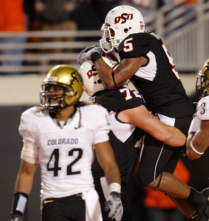 Oklahoma State running back Keith Toston, right, celebrates with teammate Andrew Mitchell, center, following a touchdown against Colorado in the fourth quarter of an NCAA college football game in Stillwater, Okla., Thursday, Nov. 19, 2009. Colorado's Benjamin Burney is at left. Oklahoma State won the game 31-28. (AP Photo/Sue Ogrocki)