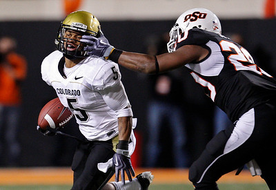 Oklahoma State linebacker Andre Sexton, right, moves in to tackle Colorado tailback Rodney Stewart, left, in the third quarter of an NCAA college football game in Stillwater, Okla., Thursday, Nov. 19, 2009. (AP Photo/Sue Ogrocki)