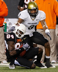 Oklahoma State wide receiver Hubert Anyiam, left, catches a pass in front of Colorado defender Jimmy Smith, right, in the fourth quarter of an NCAA college football game in Stillwater, Okla., Thursday, Nov. 19, 2009. Oklahoma State won the game 31-28. (AP Photo/Sue Ogrocki)