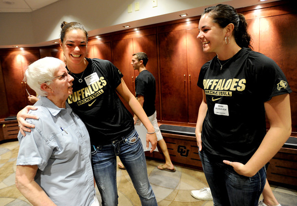 "Julie Hammarstrom gets a hug from CU basketball player, Meghan Malcolm-Peck as sister, Brenna looks on. Hammarstrom has known the girls all their lives.<br /> The University of Colorado Athletic Department held the grand opening of the new practice facilities for volleyball and basketball on Saturday.<br /> For more photos of the new facility, go to  <a href=""http://www.dailycamera.com"">http://www.dailycamera.com</a><br /> Cliff Grassmick / August 20, 2011"