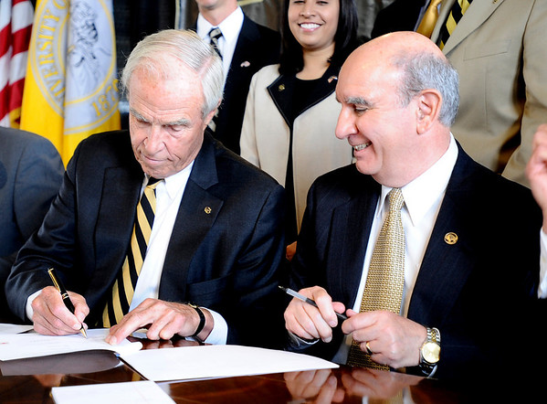 Chancellor Philip DiStefano (cq)(right) smiles while President Bruce Benson signs one of the documents moving the University of Colorado to the PAC 10 during a Regents meeting at the University of Colorado in Boulder, Colorado June 11, 2010.  CAMERA/Mark Leffingwell