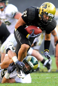 CU's Scotty McKnight (21) is taken down by CSU's Alex Williams (51) at the annual Rocky Mountain Showdown in Folsom Field in Boulder, Colorado on Sunday, Sept. 6, 2009. KASIA BROUSSALIAN / THE CAMERA