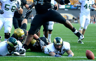 CU's Marcus Burton (54) jumps over CSU's John Mosure (7) after he releases the ball at the annual Rocky Mountain Showdown in Folsom Field in Boulder, Colorado on Sunday, Sept. 6, 2009. KASIA BROUSSALIAN / THE CAMERA