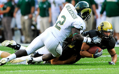 CU's Jason Espinoza (15) falls to the ground after being tackled by CSU's DeAngelo Wilkinson (2) at the annual Rocky Mountain Showdown in Folsom Field in Boulder, Colorado on Sunday, Sept. 6, 2009. KASIA BROUSSALIAN / THE CAMERA