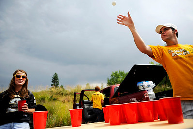 Colorado alum Matt Davis plays beer pong while CU senior Aubry Teeters watches while they tailgate before the Rocky Mountain Showdown outside of Folsom Field in Boulder, Sunday, Sept. 6, 2009. KASIA BROUSSALIAN / THE CAMERA