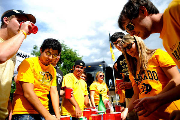 CU senior John Fuhrman (right), Alison Sweeney (far right), Pat Lyman and Tommy Manchego play flip cup while they tailgate before the Rocky Mountain Showdown outside of Folsom Field in Boulder, Sunday, Sept. 6, 2009.<br /> KASIA BROUSSALIAN / THE CAMERA