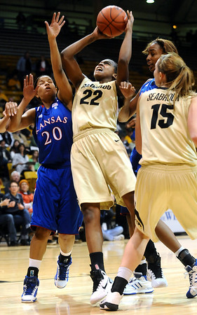 CUKANSAS<br /> CU's Brittany Spears shoots while under pressure from Diara Moore, left, and Carolyn Davis of Kansas.<br /> Photo by Marty Caivano/Jan. 12, 2011