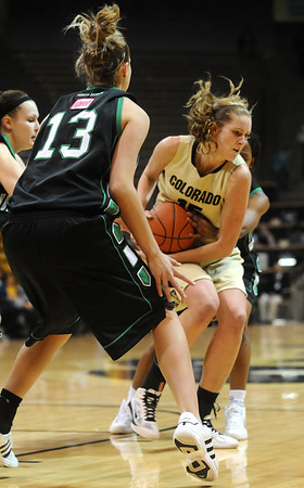 CU<br /> CU's Julie Seabrook holds onto the ball despite pressure from North Dakota, including forward Madi Buck, number 13.<br /> Photo by Marty Caivano/Jan. 4, 2010