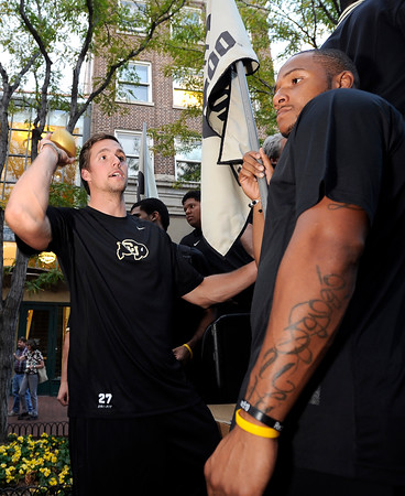 """University of Colorado football players Tommy Papilion, left, throws a football to a fan while standing next to teammate Davaughn Thornton, right, on Friday, Aug. 31, during the CU pep rally on Pearl Street in Boulder. For more photos and video of the pep rally go to  <a href=""""http://www.dailycamera.com"""">http://www.dailycamera.com</a><br /> Jeremy Papasso/ Camera"""