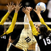 Colorado's Anicia Santos slams the ball by Missouri's Paola Ampudia (left) and Catie Wilson (right) during their volleyball game at the University of Colorado in Boulder, Colorado November 3, 2010. CAMERA/Mark Leffingwell