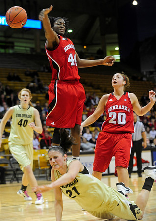 CUNEB<br /> CU's Chelsea Dale takes a tumble after being fouled by Katya Leick, right, of Nebraska. At left is Nebraska's Catheryn Redmon.<br /> Photo by Marty Caivano/Feb. 6, 2011