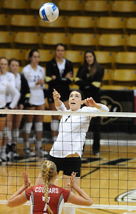 VOLLEY CU's Kelsey English jumps to drive the ball past Rachel Todorovich of Washington State.   PHOTO BY MARTY CAIVANO Nov. 18, 2011