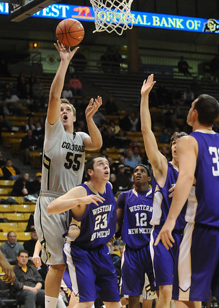 CU<br /> CU's Trey Eckloff shoots over Ryan Crane, left, and TJ Riley of Western New Mexico.<br /> Photo by Marty Caivano/Jan. 5, 2010