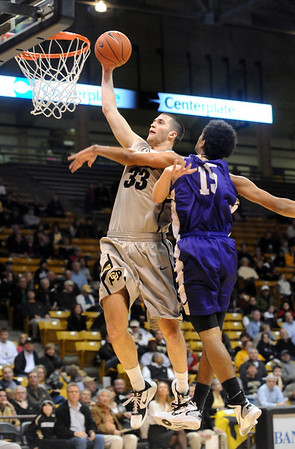 CU<br /> CU's Austin Dufault sinks a dunk despite pressure from Nate Murdock of Western New Mexico.<br /> Photo by Marty Caivano/Jan. 5, 2010