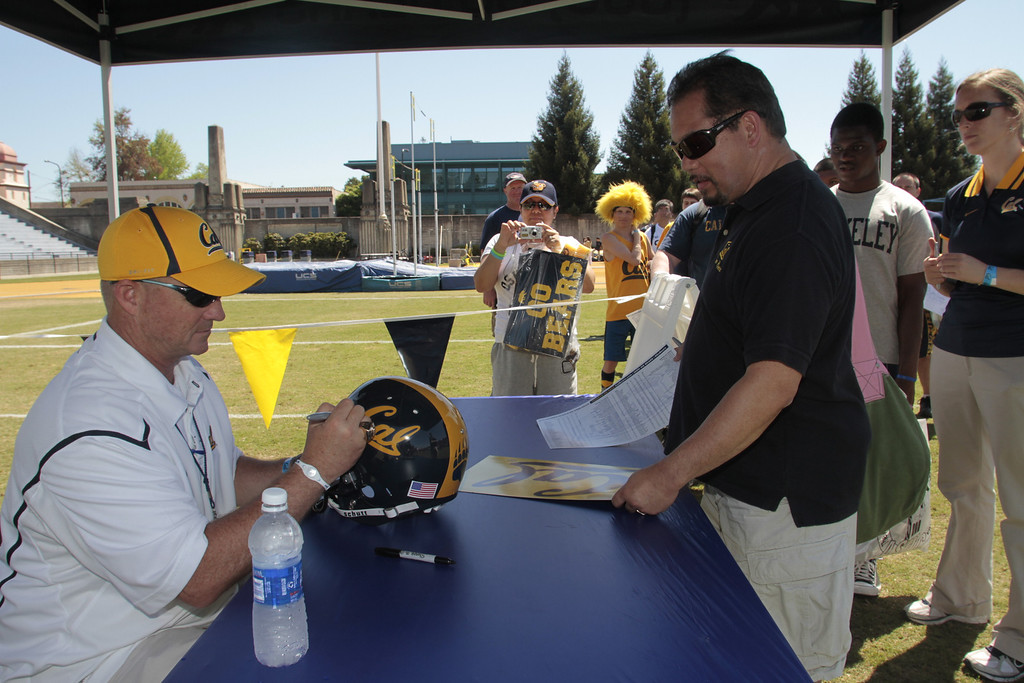 Head coach Jeff Tedford signs an autograph for Ted  Aranas during the Cal Football Spring practice at Edwards Stadium in Berkeley, Calif. on Saturday, April 21st, 2012.