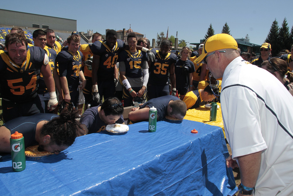 Head coach Jeff Tedford blows a whistle to start the pie eating contest during the Cal Football Spring practice at Edwards Stadium in Berkeley, Calif. on Saturday, April 21st, 2012.