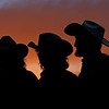 Sunset silloetted these cowboys as they watched and refreshed