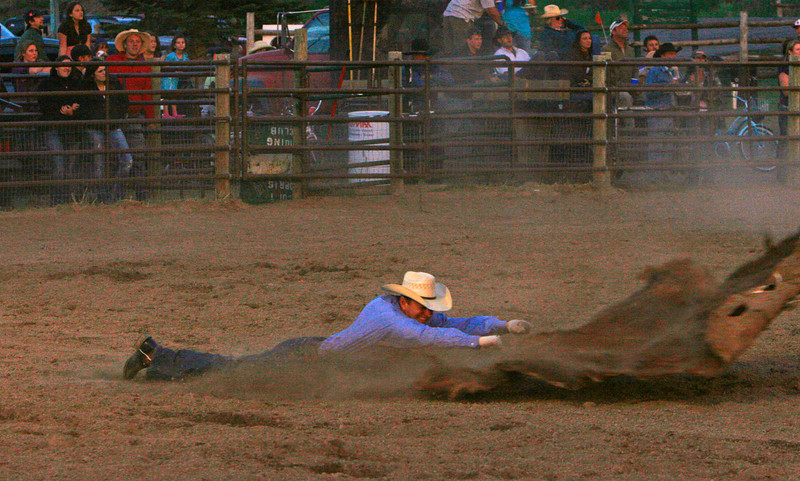 The cowhide is jerked out of the cowboys hands while the cowboy is airborne.
