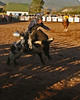 A Bull rider leans into the lunge of the bull.