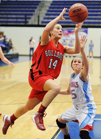 Globe/T. Rob Brown<br /> Carl Junction's Sydney Koch attempts a shot under the basket as Webb City's Mikaela Burgess plays defense during the District 12 Class 4 Basketball Tournament Thursday evening, Feb. 28, 2013, at Carthage High School's gymnasium.