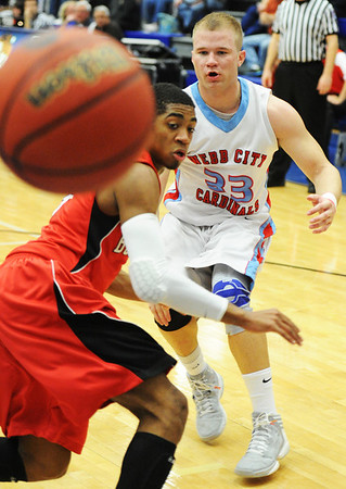 Globe/T. Rob Brown<br /> Webb City's Kohl Slaughter passes the ball past Carl Junction's Matthew Magee during the District 12 Class 4 Basketball Tournament Friday evening, March 1, 2013, at Carthage High School.