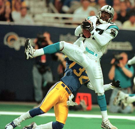 11/14/99 Carolina Panther wide receiver (87) Muhsin Muhammad pulls in a pass from quarterback Steve Beuerlein Sunday as St. Louis Rams' (32) cornerback Dre' Bly applies pressure.