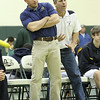 St. Pius X head wrestling coach David Sabino, left, and assistant coach Dan Hovey try to employ some body motion as they watch one of their sophomore wrestlers in a 126-pound weight class match.