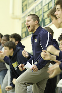 Marist School head wrestling coach Riddick Beebe, center, and team members along the sideline, react to freshman Joseph Geeslin's wrestling victory in his 106-pound weight division match.