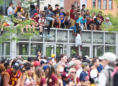 KRISTIN BAUER | GAZETTE Fans hoist one another on top of shelters, bus stops, and garages to watch the Cleveland Cavaliers parade down the streets of Cleveland in celebration of the NBA Championship title.