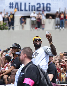 KRISTIN BAUER | GAZETTE LeBron James takes a photo as he rides in the parade celebrating the Cleveland Cavaliers' championship title.