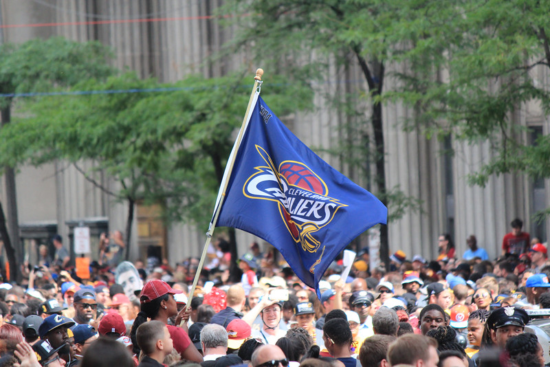 HALEE HEIRONIMUS / GAZETTE A Cavaliers flag was hoisted above celebrating fans during the downtown Cleveland parade on Wednesday.