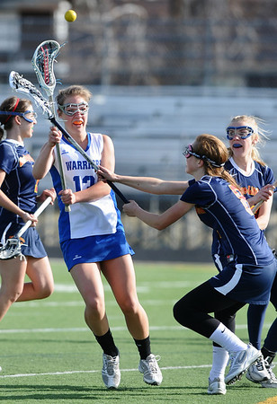LACROSSE<br /> Carley Dvorak passes the ball while under pressure from Alexis Stein of Heritage.<br /> Photo by Marty Caivano/March 29, 2011