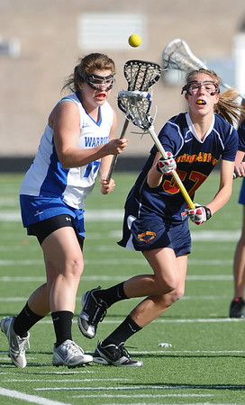 LACROSSE<br /> Gabby Wallace of Centaurus tries to control the ball under pressure from Stacey Zuppa of Heritage.<br /> Photo by Marty Caivano/March 29, 2011