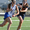 LACROSSE<br /> Sarah Brown drives past Madison Hosack of Heritage.<br /> Photo by Marty Caivano/March 29, 2011