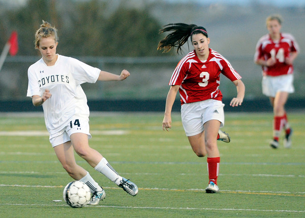 "Monarch High School's Kate Yeash, left, dribbles the ball past Centaurus High School's Danelle Dondelinger on Friday, March 16, during a soccer game against at Monarch High School in Louisville. For more photos of the game go to  <a href=""http://www.dailycamera.com"">http://www.dailycamera.com</a><br /> Jeremy Papasso/ Camera"