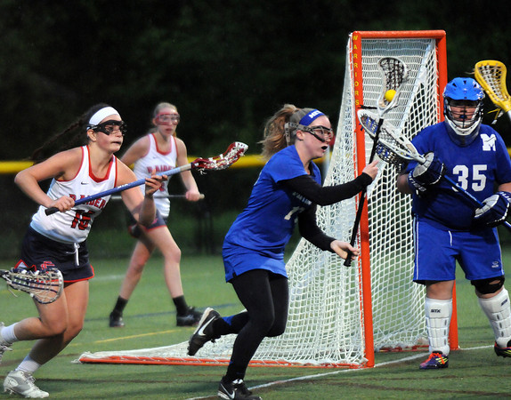 CARL RUSSO/Staff photo. Central Catholic defeated Methuen 15-5 in Girls Lacrosse Division I North First Round Tuesday night. Methuen captain, Ashley Horan scoops up the loose ball as Central's Vanessa Pino gives chase. 5/27/2014.