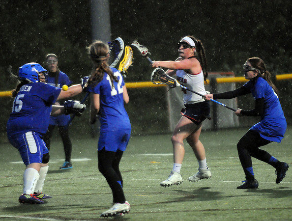 CARL RUSSO/Staff photo. Central Catholic defeated Methuen 15-5 in Girls Lacrosse Division I North First Round Tuesday night. Central's Vanessa Pino scores against Methuen's goalie, Sophia Tiar as Methuen's Megan Bruneau, right comes up from behind to defend. 5/27/2014.