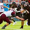 Record-Eagle/Brett A. Sommers Elk Rapids running back Nick Aseritis stiff arms Charlevoix defensive back Brad Klinger during Friday's game in Elk Rapids. The Rayders won 45-13.